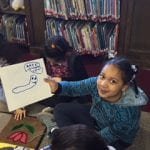 Student holding her drawing on a whiteboard of a caterpillar.