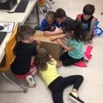 5 students sitting on floor, decorating cardboard box with crayons