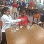 Two students sitting at a table making a structure from toothpicks and marshmallows.