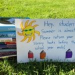 stack of books behind a sign on the lawn, reminding students to return library books