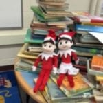 two holiday elves resting on a stack of books