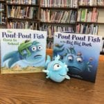 two books and blue stuffed toy fish displayed on a library shelf