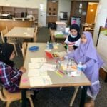 Students working on school assignment at tables.