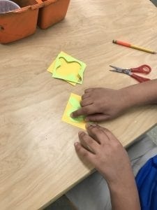 student hands arranging the shape they cut out onto a different colored square