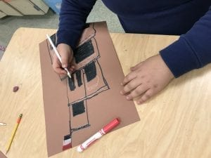 student hands drawing a building from Yemen with a Yemen flag on top