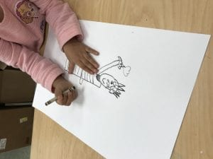student hands drawing the statue of liberty