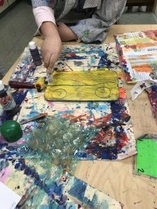 Image of student's hands drawing lines with a fork into wet paint with different materials on the table around them
