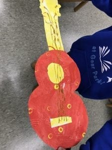 Example of student's paper guitar that is all warm colors with glitter glue stings