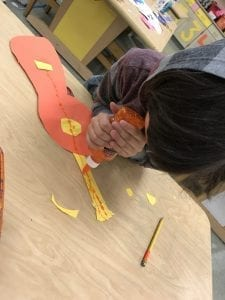 Student using glitter glue to apply lines to show the strings of his paper guitar