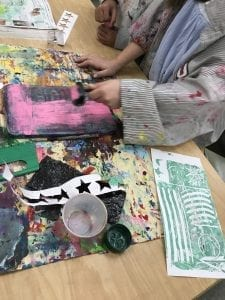 image of a student rolling paint on their printing plate with a brayer