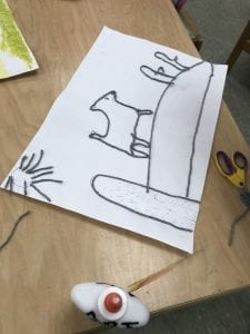 student working on a yarn painting showing an animal on a hill with a sun in the sky