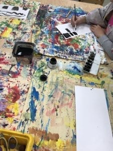 Image of student table with student working on mixing ink and water with a brush