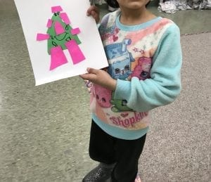 student holding artwork with a monster the shape of a triangle with rectangles for arms, legs, and hair