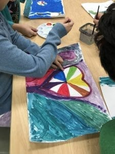 a student painting a color wheel inside of a heart; some of the color shave been painted and some are still white