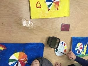 three students' hands painting