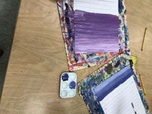 student papers in progress that show purple and indigo stripes of paint that get darker as they move down the paper