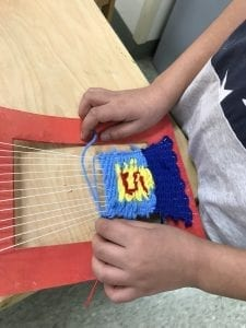 """student hands weaving a tapestry tat looks like the super man logo with a yellow pentagon with a red """"S"""" in the middle and blue all around it"""