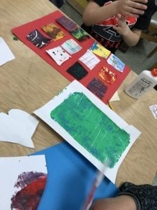 Student cutting colorful papers into rectangles and arranging them on a larger red paper