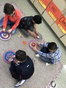group of four male students weaving on the floor looking down at their weavings