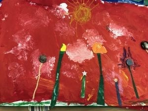 student collage of paper and button flowers in front of a painted red sky with a few white clouds and a yellow sun