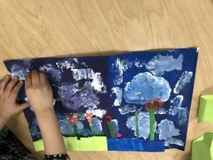 student's hands gluing down a piece of paper to their collage that has a dark blue and purple sky with white clouds and a few red flowers with green stems made out of paper