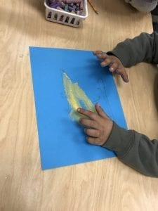 student's fingers blending the chalk on a blue paper