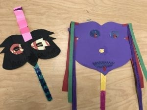 Two student made masks made out of paper, they are both symmetrical