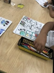 student hands coloring in their comic with colored pencils