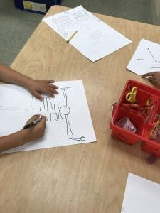 students' hands drawing insects on white papers