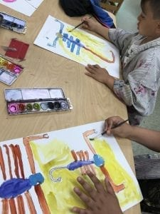 two students painting in their drawings of what look to be scorpions