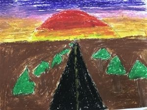 A student drawing of a road in the middle of the paper with dirt and trees on each side of the road; a sunset is drawn in the sky