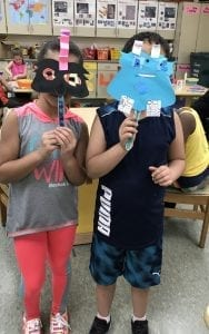 Two students holding up paper masks in front of their faces