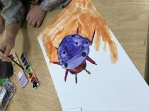 student's hands painting a lady bug drawing with watercolor paints