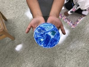 student hands holding his dot, it is colored in blue