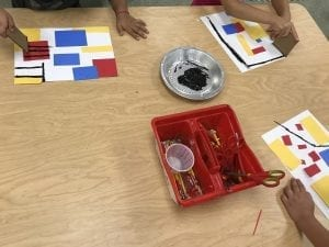 student hands holding a small piece of cardboard, a black tray of paint is on the center of the table, they are stamping the cardboard on their papers to create black lines with the paint