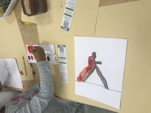 student painting with red paint around their drawing of a bubble person walking