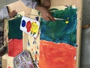 student's hands painting a paper that is half green and half orange; there are primary colored paints on the table