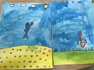 two student paintings; one has a bubble person holding a balloon and floating away, the other has a bubble person doing a handstand on the ground