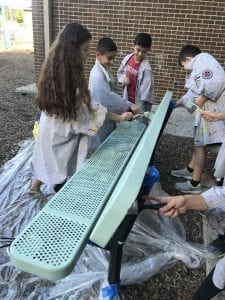six students wearing large paint smocks painting a blue bench