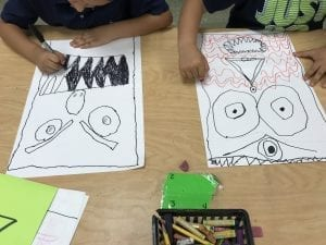 photo of students' hands drawing monsters
