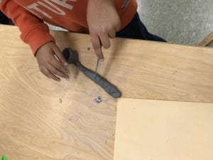student hands working on their clay spoon