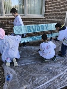 """four students kneeling down painting a blue bench, the bench says the word """"Buddy"""" on the top of it; there is a tarp on the ground"""