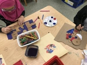two students painting pieces of cardboard that have been cut and glued together