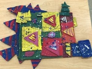 student artwork that has varisou shapes cut from cardboard and is painted with many colors, it also has splatter paint designs