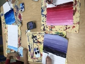 student hands painting value scales; one color but different values of the color that go from light to dark