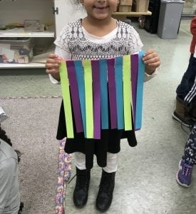 student holding a small strips of paper that have been glued together at the top and are arranged in a pattern