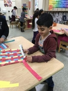 student holding a glue bottle and gluing down a strip of paper in his weaving