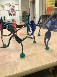 several colorful sculptures that are the shape of people doing different poses, their feet are stuck in pieces of clay