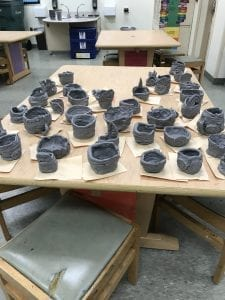 many clay bowls/cups sitting on a table, they are made from coils and are different sizes