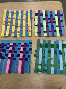 four examples of student artwork; weaving made with different colored paper with small lines and shapes drawn on top with black marker and glitter glue